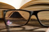 stock photo of humble  - reading glasses with bokks on the table - JPG