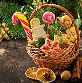 image of lollipop  - Christmas gingerbread cookies and lollipops in a basket on old wooden background - JPG