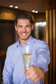 pic of flute  - Handsome man holding flute of champagne at the bar - JPG