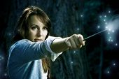 stock photo of magic-wand  - Teenage wizard girl with magic wand casting spells in a enchanted fantasy forest - JPG