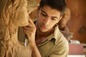 stock photo of carving  - Man people job young student at work learning craftsman profession in art class working with wooden statue and carving wood - JPG