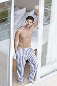 image of partially nude  - Full length portrait of handsome young man standing at balcony doorway - JPG