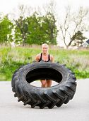 image of strongman  - Young female athlete doing tire - JPG