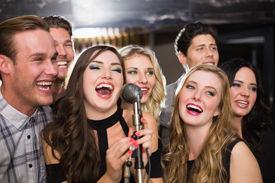 stock photo of karaoke  - Happy friends singing karaoke together at the bar - JPG