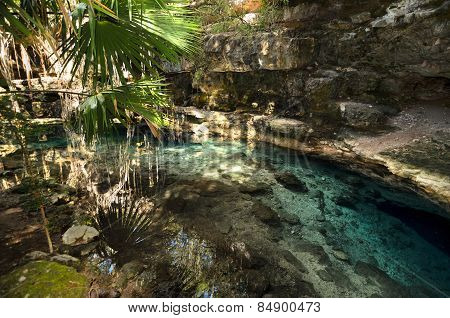 X-batun Cenote - Natural Lagoone With Transparent Turquoise Water Surrounded By Rocks And Tropical V