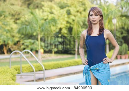 Woman standing at poolside and day dreaming