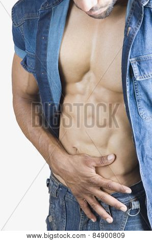 Close-up of a macho man checking his abdominal muscles