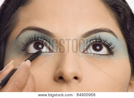Person's hand applying eye liner on a young woman