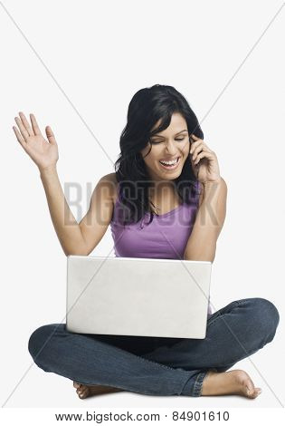 Successful woman talking on a mobile phone and clenching fist