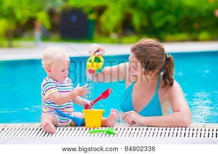 Mother And Baby Playing In Swimming Pool