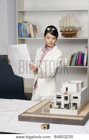 Businesswoman holding a blueprint and looking at a model home in an office