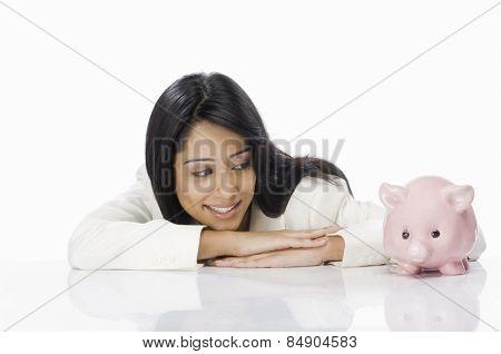 Businesswoman looking at a piggy bank