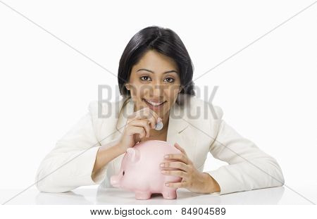 Businesswoman inserting a coin into a piggy bank