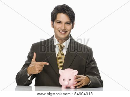 Portrait of a businessman pointing towards a piggy bank