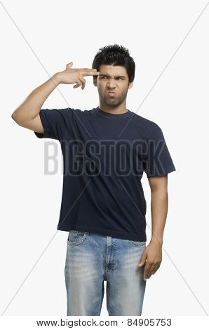 Man making gun sign with fingers at his head