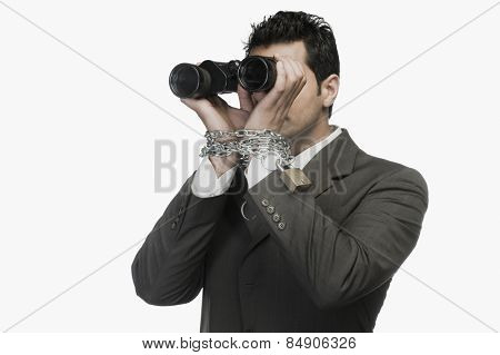Businessman locked in chains and looking through binoculars