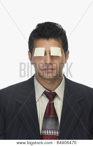 Adhesive notes on a businessman's eyes