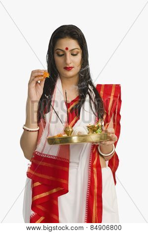 Woman in a Bengali sari holding pooja thali