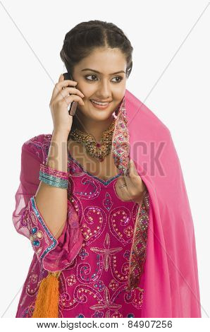 Woman wearing a salwar kameez and talking on a mobile phone