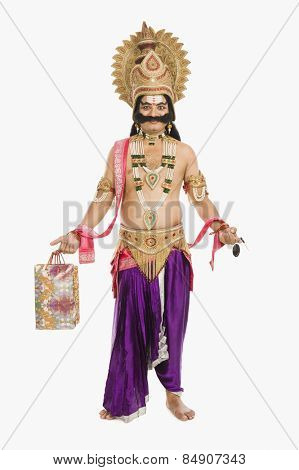 Stage artist dressed-up as Ravana holding a shopping bag