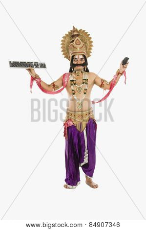 Man dressed-up as Ravana holding keyboard and mouse