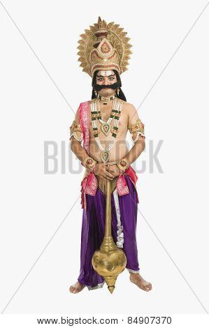 Artist dressed-up as Ravana the Hindu mythological character and holding a mace