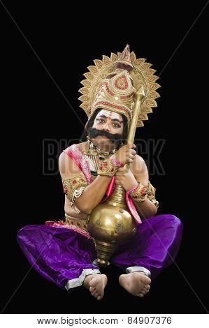 Man dressed-up as Ravana the Hindu mythological character and holding a mace