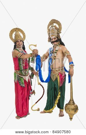 Two stage artists dressed-up as Rama and Ravana and shaking hands