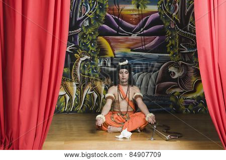 Stage artist dressed-up as Rama and praying