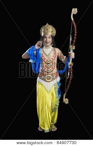 Portrait of a stage artist dressed-up as Rama the Hindu mythological character talking on a mobile phone