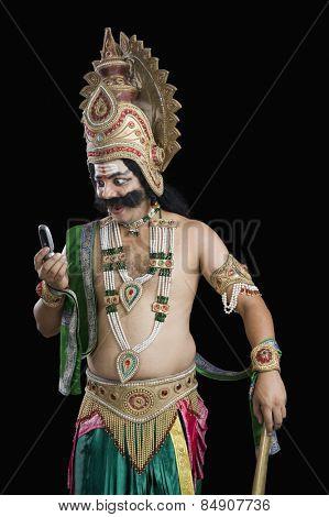 Artist dressed-up as Ravana reading text message