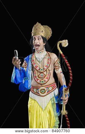 Man dressed-up as Rama reading text message