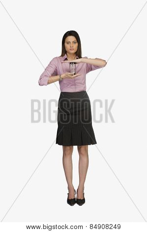 Young businesswoman holding an hourglass
