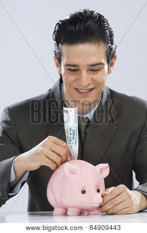 Businessman putting one hundred rupees note in a piggy bank