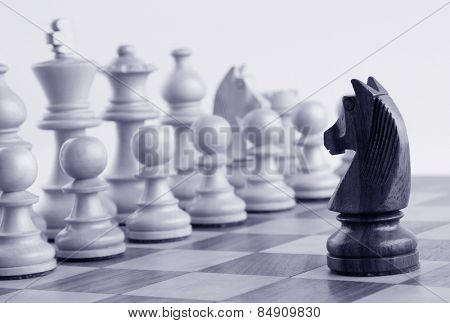 Black knight facing white chess pieces on a chess board