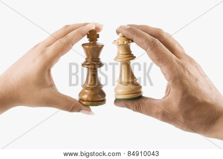 Man and woman's hands holding chess king and queen