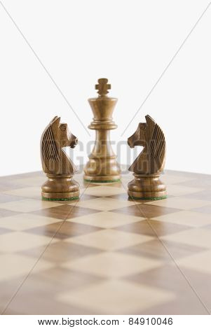 Close-up of chess knights face to face with a chess king on a chessboard
