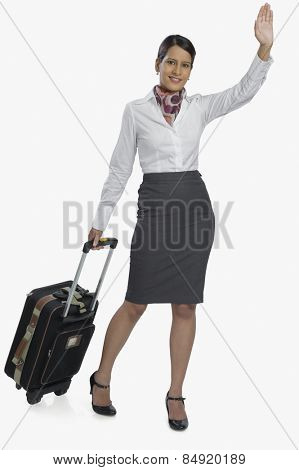 Air hostess carrying her luggage and waving
