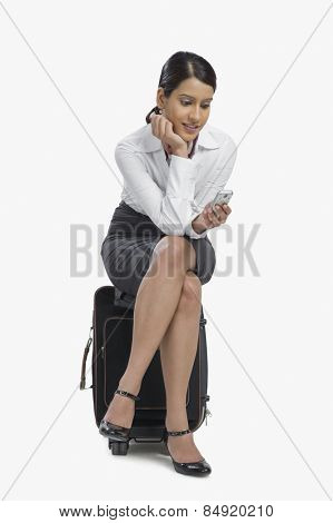 Air hostess sitting on her bag and text messaging on a mobile phone