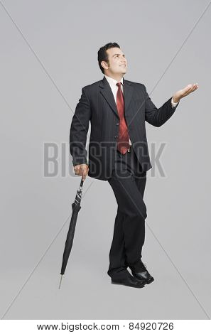 Businessman holding an umbrella and checking for rain
