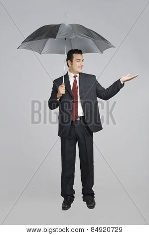 Businessman under an umbrella checking for rain
