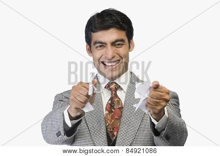 Businessman smiling and tearing a sheet of paper