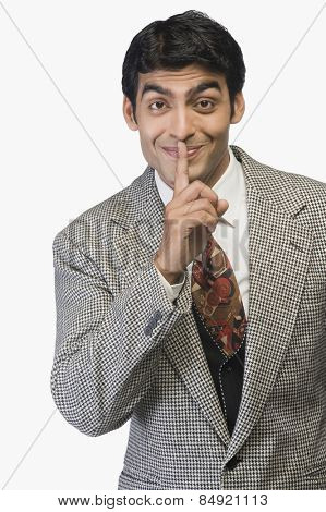 Portrait of a businessman with finger on lips