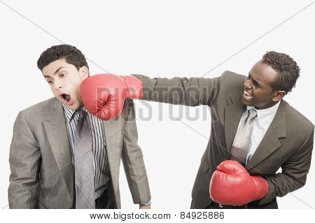 Businessman punching his co-worker with boxing gloves