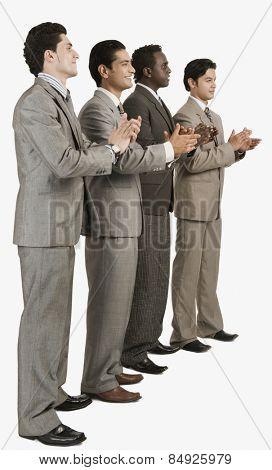 Four businessmen applauding