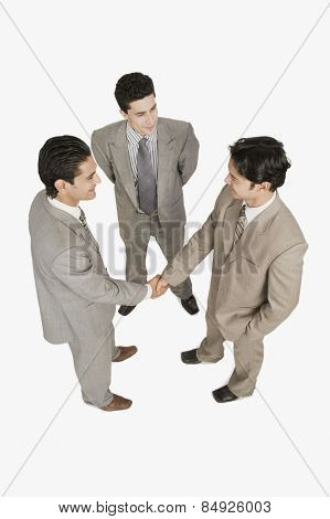 Two businessmen shaking hands with another businessman standing beside them