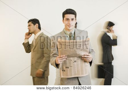 Businessman holding a newspaper with his colleagues in the background