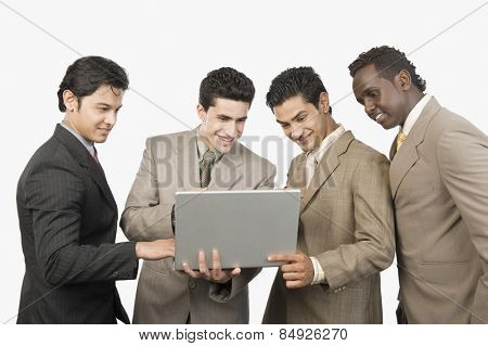 Four businessmen standing with a laptop