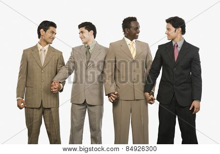 Four businessmen standing with holding hands