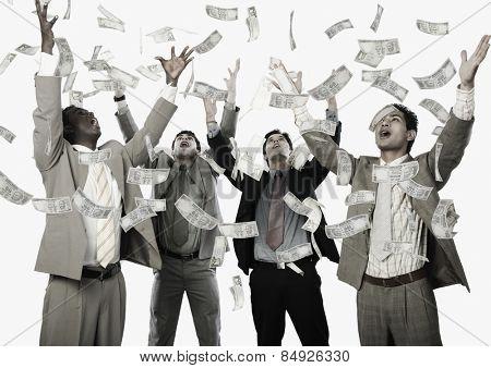 Banknotes falling over four businessmen